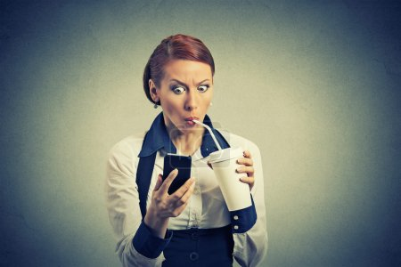 surprised business woman reading news on smart phone drinking soda coffee
