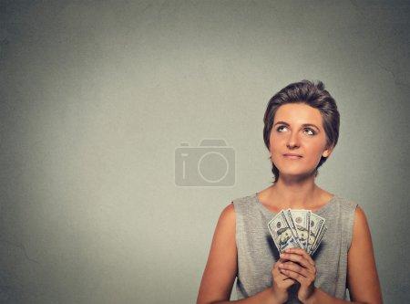 Photo pour Verticale de plan rapproché heureuse a excité la jeune femme réussie retenant des billets d'argent d'dollar dans la main recherchant l'isolement sur le fond gris de mur. Sensation positive d'expression faciale d'émotion. Récompense financière - image libre de droit
