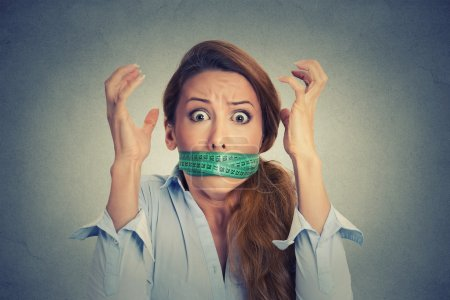Photo for Diet restriction and stress concept. Portrait of young frustrated woman with a green measuring tape around her mouth isolated on gray wall background. Face expression emotion - Royalty Free Image