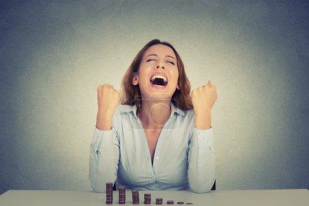 Photo pour Jeune femme d'affaires réussie assis à la table avec pile croissante de pièces célèbre poings hurlants pompé. Objectif de liberté financière concept de réussite - image libre de droit