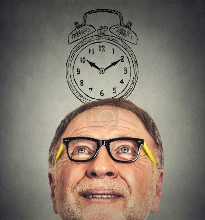 homme âgé avec des lunettes et un réveil au-dessus de sa tête regardant