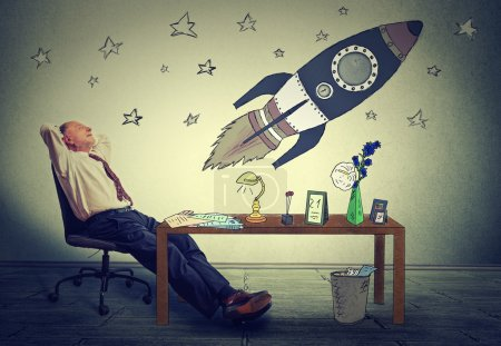 business man relaxing at his desk in office daydreaming of space tourism