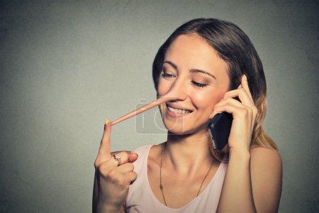 Photo pour Jeune femme heureuse avec le long nez parler téléphone mobile isolé sur fond de mur gris. Concept de menteur. Les expressions de visage humain, des émotions, des sentiments - image libre de droit