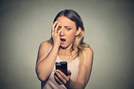 anxious scared young girl looking at phone seeing bad news