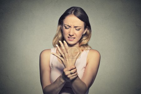 Young woman holding her painful wrist. Sprain pai