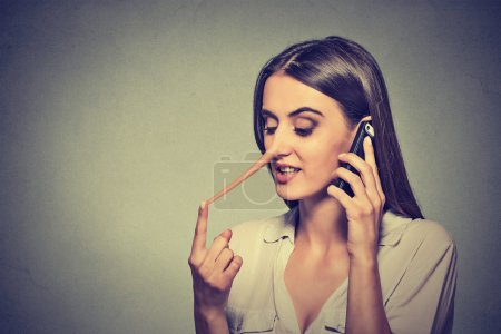 young woman talking on mobile phone telling lies has a long nose