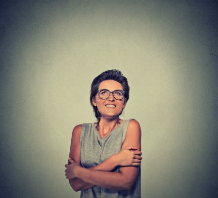smiling woman with glasses holding hugging herself