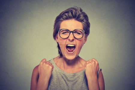 Photo for Angry young woman with glasses screaming fists up in air - Royalty Free Image
