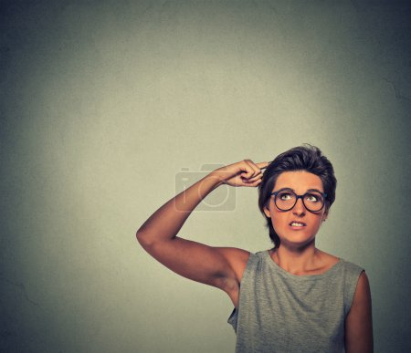 Contused thinking woman with glasses bewildered sc...