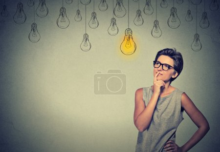 Happy smart girl with glasses and solution lightbulb above head