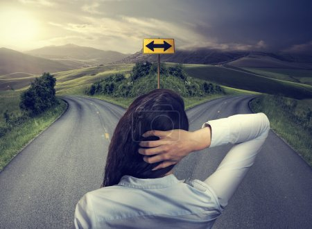Business woman in front of two roads thinking deci...