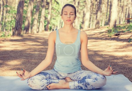 Beautiful young woman meditating outdoors in spring summer park