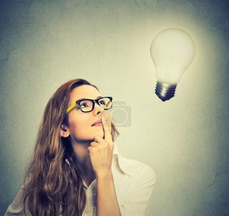 girl thinks looking up at bright light bulb