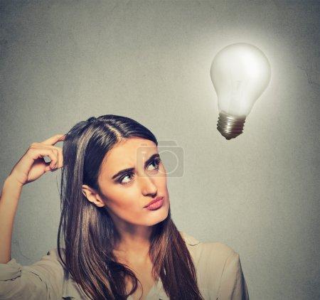 beautiful girl woman thinks looking up at bright light bulb