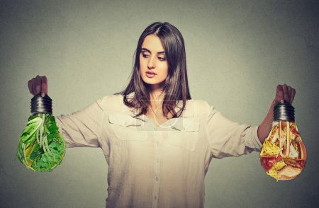 Woman thinking making diet choices junk food or green vegetables