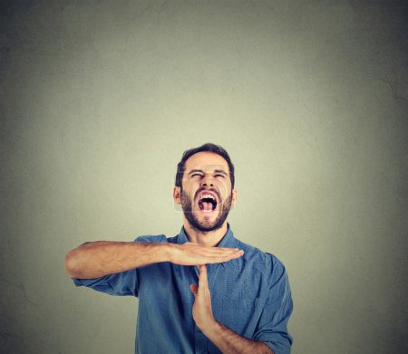 Photo pour Young man showing time out hand gesture, frustrated screaming to stop isolated on grey wall background. Too many things to do. Human emotions face expression reaction - image libre de droit