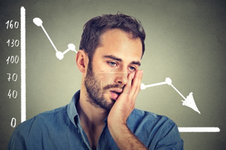 frustrated stressed young man desperate with financial market chart graphic going down