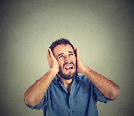 Photo pour Portrait jeune agacé, malheureux, stressé homme couvrant ses oreilles, en levant, à dire, cesser de faire grand bruit, m'envoie-t-il des maux de tête isolé sur fond gris avec espace de copie. Réaction d'émotion négative - image libre de droit