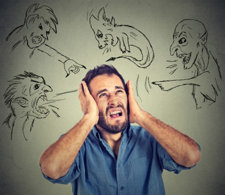 Stressed young man covers his ears with his hands evil guys pointing fingers at him