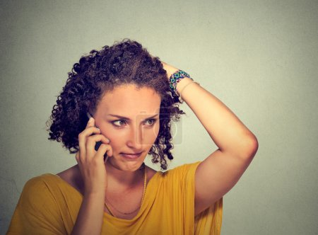 Unhappy young woman talking on mobile phone looking down stressed