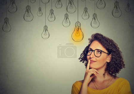 thinking woman in glasses looking up with light idea bulb above head