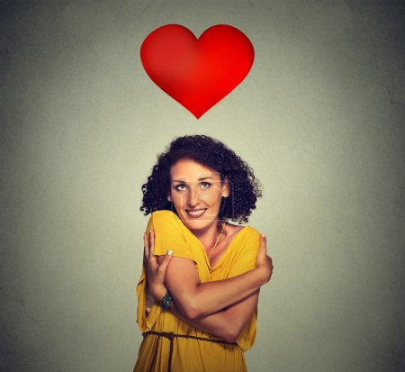 portrait smiling woman holding hugging herself with red heart above head