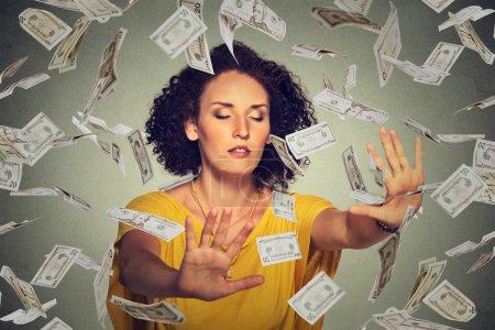 Photo pour Femme d'affaires jeune entrepreneur les yeux fermés essayant d'attraper des billets de banque billets de dollar volant dans les airs sur fond de mur gris. Concept de réussite financière de l'entreprise ou défi de crise - image libre de droit