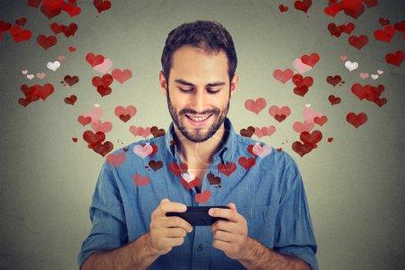 Photo pour Portrait homme heureux envoyant un SMS d'amour sur un téléphone portable avec des cœurs rouges s'envolant de l'écran isolé sur fond gris mur. Les émotions humaines - image libre de droit