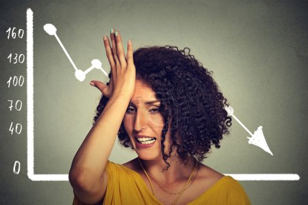 Frustrated stressed business woman with financial chart graphic going down