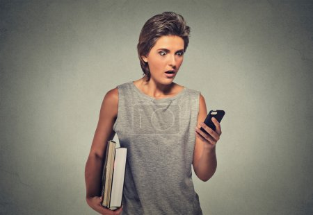 nxious looking young woman starring at cell phone seeing bad news or photos