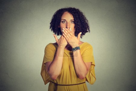 woman covering closed mouth with hands. Speak no evil concept