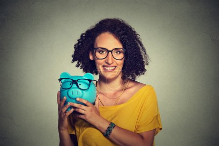 Piggybank and woman wearing glasses