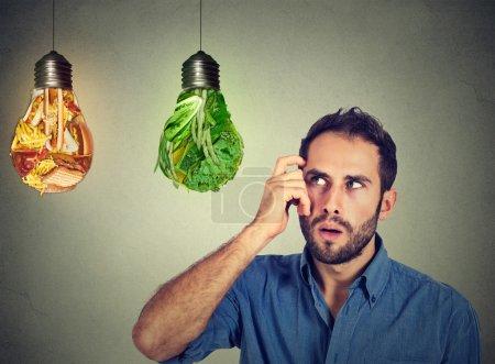 Photo pour Homme perplexe pensant à la malbouffe et légumes verts en forme d'ampoules prenant la décision isolé sur fond gris. Choix du régime alimentaire bonne nutrition mode de vie sain concept de bien-être - image libre de droit