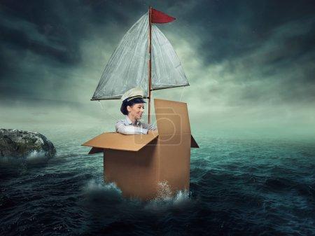 Photo pour Femme voyageant par l'eau. Liberté de bonheur. Heureux souriant jeune capitaine femme entrepreneur. Conçu le navire imaginaire issu de boîte de carton - image libre de droit
