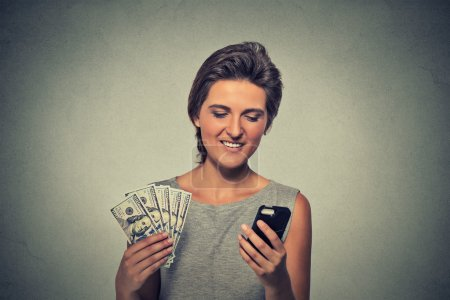 Excited woman with smart phone and dollar banknotes isolated on gray wall background