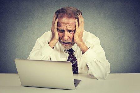 Photo pour Portrait homme stressé senior travaillant sur ordinateur portable assis à la table isolé sur fond de mur gris - image libre de droit
