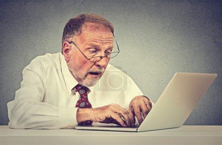 Photo pour Confus surpris homme âgé en utilisant un ordinateur portable PC - image libre de droit