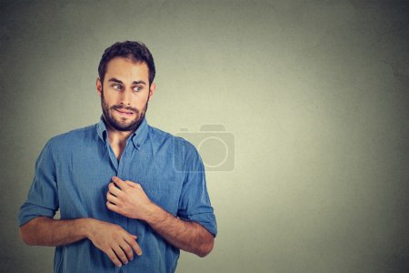 young man in unpleasant, awkward situation, playing nervously with hands. Embarrassment