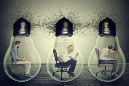 Company employees sitting in row inside electric lamp light bulb using laptop