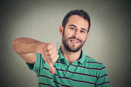 sarcastic young man showing thumbs down sign hand gesture