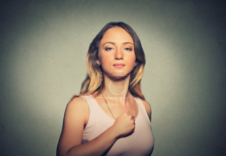 Superhero girl. Confident young woman isolated on gray wall background