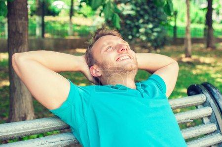 Photo pour Portrait rapproché d'un beau jeune homme heureux en chemise regardant vers le haut dans la pensée, relaxant sur un banc isolé sur fond de parc - image libre de droit
