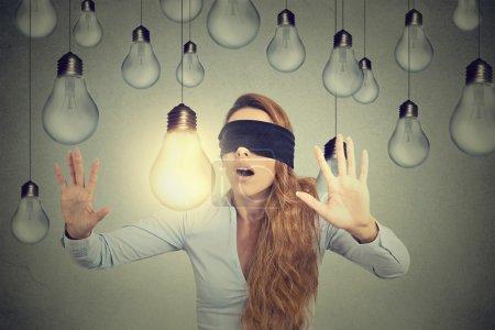 Photo pour Jeune femme les yeux bandés marchant à travers les ampoules à la recherche d'une idée lumineuse - image libre de droit