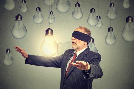 Blindfolded senior man walking through light bulbs searching for bright idea