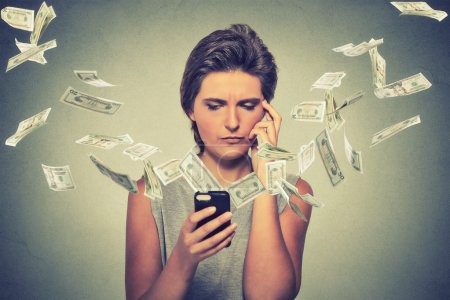 Thoughtful young woman using smartphone with dollar bills banknotes flying away