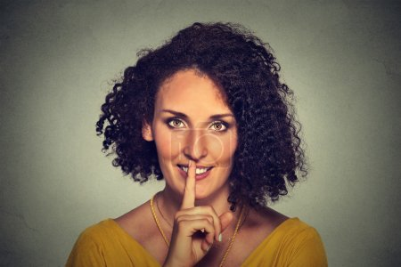 happy young woman placing finger on lips asking shhhhh, quiet, silence