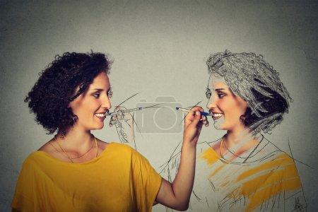 Photo pour Créez-vous, votre concept d'image. Jeune femme attirante dessinant une image, croquis d'elle-même isolée sur le fond gris de mur. Expressions du visage humain, détermination, créativité - image libre de droit
