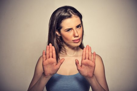 annoyed angry woman with bad attitude gesturing with palms outward to stop