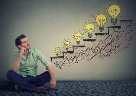 Photo pour Homme heureux s'asseyant sur un plancher dans son bureau rêvant du succès d'éducation d'affaires, de la promotion, de la croissance d'entreprise fond isolé de texture grise de mur. Type beau recherchant à croissant des ampoules - image libre de droit