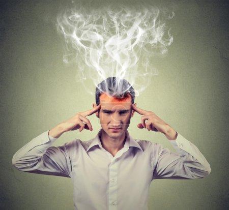 Foto de Hombre piensa muy intensamente tener dolor de cabeza aislado en el fondo de la pared gris. expresión de rostro humano - Imagen libre de derechos